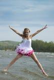 Junge schöne Frau, die auf den Strand springt. Stockfotos