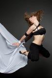 Junge schöne Frau, die auf ein Schwarzes springt Stockfotos