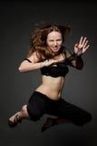 Junge schöne Frau, die auf ein Schwarzes springt Lizenzfreies Stockfoto