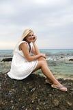 Junge schöne Frau, die auf einem nahen Steinmeer sitzt Lizenzfreies Stockbild
