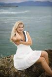 Junge schöne Frau, die auf einem nahen Steinmeer sitzt Lizenzfreie Stockbilder