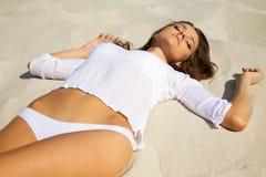 Junge schöne Frau, die auf Strand legt Lizenzfreie Stockfotos
