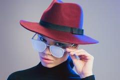 Junge schöne Frau, die den breitrandigen Hut, Kamera über der Sonnenbrille betrachtend bedeckt trägt stockfoto