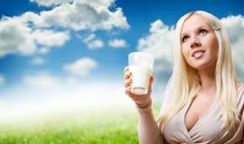 Junge schöne Frau, die ein Glas Milch isst. lizenzfreies stockbild