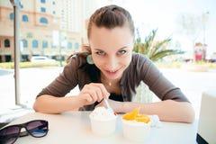 Junge schöne Frau, die Eiscreme isst Stockfotografie