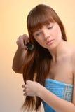 Junge schöne Frau, die ihr Haar kämmt Stockfotografie