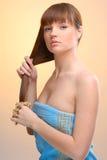 Junge schöne Frau, die ihr Haar kämmt Lizenzfreie Stockfotografie