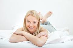Junge schöne Frau, die im Bett liegt Lizenzfreie Stockfotos