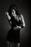Junge schöne Frau, die im schwarzen Kleid aufwirft Stockfotos