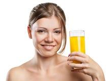 Junge schöne Frau, die Orangensaft trinkt stockbilder