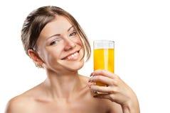 Junge schöne Frau, die Orangensaft trinkt stockfotos