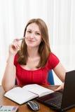 Junge schöne Frau, die am Tisch mit einem Laptop sitzt, Stockbilder
