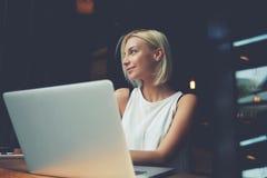 Junge schöne Frau, die tragbares Netzbuch während der Erholungszeit in der Caféstange verwendet Stockfoto