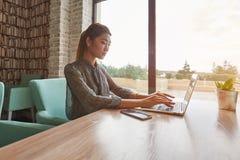Junge schöne Frau, die tragbares Netzbuch während der Erholungszeit in der Caféstange verwendet Lizenzfreie Stockfotos