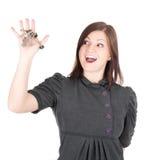 Junge schöne Frau, die Wohnungstasten auf weißem Hintergrund zeigt Lizenzfreie Stockfotos