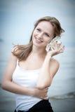 Junge schöne Frau, die zu einem Seashell hört Lizenzfreie Stockfotografie