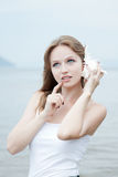 Junge schöne Frau, die zu einem Seashell hört Lizenzfreie Stockbilder