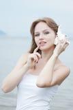 Junge schöne Frau, die zu einem Seashell hört Lizenzfreie Stockfotos
