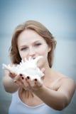 Junge schöne Frau, die zu einem Seashell hört Stockfotos
