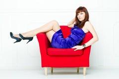 Junge schöne Frau in einem roten Stuhl stockfotografie