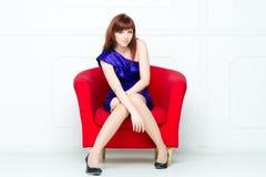 Junge schöne Frau in einem roten Stuhl stockfoto