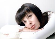 Junge schöne Frau hinter dem Schreibtischdenken lizenzfreies stockbild