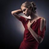 Junge schöne Frau im roten Kleid auf der Dunkelheit Lizenzfreies Stockfoto