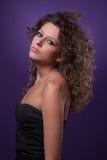 Junge, schöne Frau mit dem lockigen Haar auf Purpur lizenzfreie stockfotos