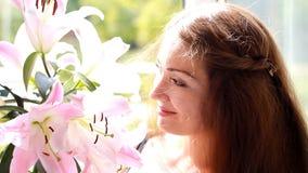Junge schöne Frau mit Lilie Nettes Mädchen riecht den Geruch von Blumen stock video footage