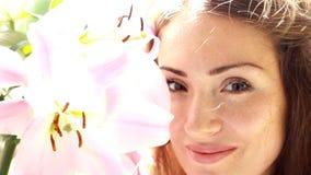 Junge schöne Frau mit Lilie Nettes Mädchen riecht den Geruch von Blumen stock video