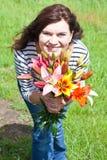 Junge schöne Frau mit Lilienblumenstrauß in den Händen stockbilder