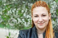 Junge schöne Frau mit orange afrikanischen Flechten Stockfotografie