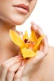Junge schöne Frau mit Orchidee lizenzfreie stockfotografie