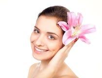 Junge schöne Frau mit rosafarbener Blume Stockbild