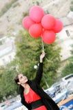 Junge schöne Frau mit roten Ballonen Stockfoto