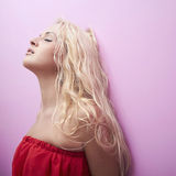 Junge schöne Frau Rotes Kleid Sexy Blondine Blondes Mädchen Gelockte Frisur Rosafarbene Wand Lizenzfreies Stockfoto