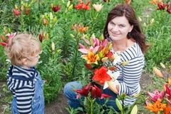 Junge schöne Frau und blondes Kleinkind mit Lilie Lizenzfreies Stockfoto