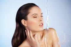 Junge schöne Frau unter dem Strom des Wassers lizenzfreies stockfoto