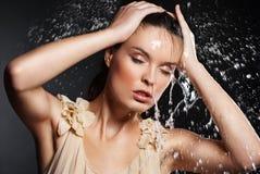 Junge schöne Frau unter dem Strom des Wassers lizenzfreie stockbilder