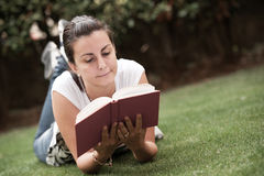 Junge schöne Frauenlagen auf grünem Feld lizenzfreies stockfoto