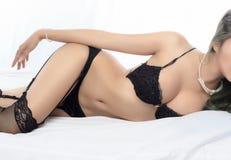 Junge schöne gebräunte sexy Asiatin, die elegante Wäsche trägt Stockfoto