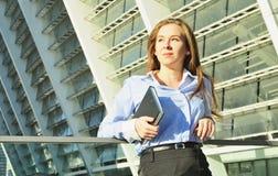 Junge schöne Geschäftsdame, die in der Bürokleidung sich lehnt auf dem Geländer und hält ein Notizbuch steht stockbilder