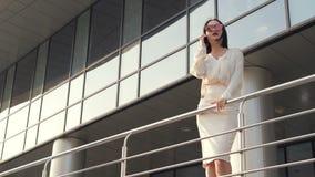 Junge schöne Geschäftsfrau, die draußen auf der Straße der Stadt und des Gebrauches ein Telefon, lächelnd bleibt, Gefühl glücklic stock video