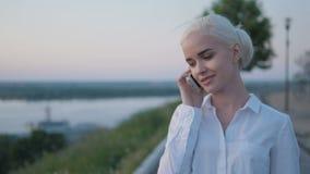 Junge schöne Geschäftsfrau, die draußen einen Telefon-Anruf auf dem Sonnenuntergang macht stockbild