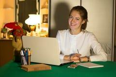Junge schöne Geschäftsfrau, die ein Haus am Laptop in einer gemütlichen Umwelt laufen lässt Freiberufler arbeitet im Haus Stockfotografie