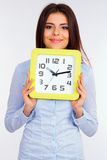 Junge schöne Geschäftsfrau, die eine Uhr hält Stockbild