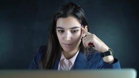 Junge schöne Geschäftsfrau, die an einem Tisch mit einem Laptop sitzt Am Abend arbeitet ein weiblicher Freiberufler entfernt stock video