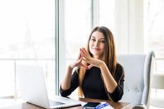 Junge schöne Geschäftsfrau, die an Laptop arbeitet und Hand auf Kinn beim Sitzen an ihrem Arbeitsplatz hält lizenzfreie stockbilder
