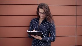 Junge schöne Geschäftsfrau, die mit den Dokumenten stehen nahes Geschäftsgebäude arbeitet stock video