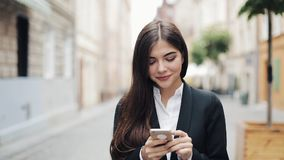 Junge schöne Geschäftsfrau, die Smartphone verwendet und auf die alte Straße geht Sie das Internet surfend Konzept: neu stock video